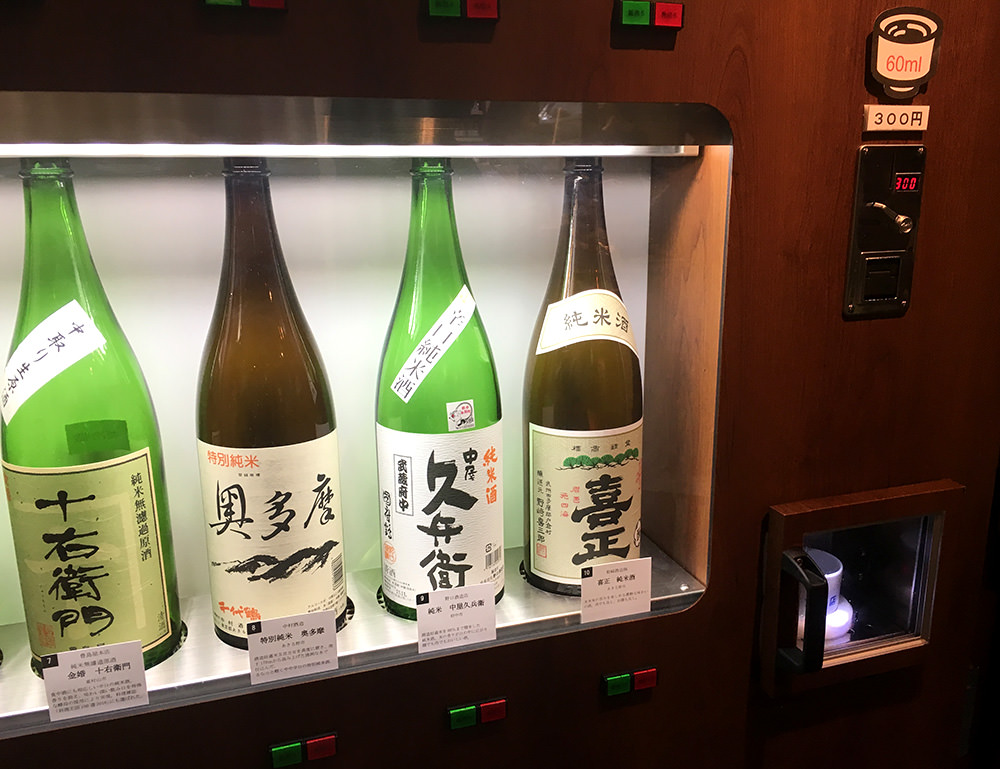Put the cup and insert the coins, then push the button under sake bottles.